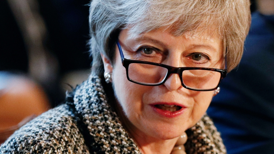 A close-up photograph of Britain's Prime Minister Theresa May who is wearing dark-rimmed glasses.