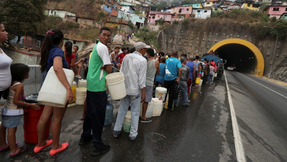 Dozens of people are shown standing in linewith buckets and other containers to collect water in Caracas.