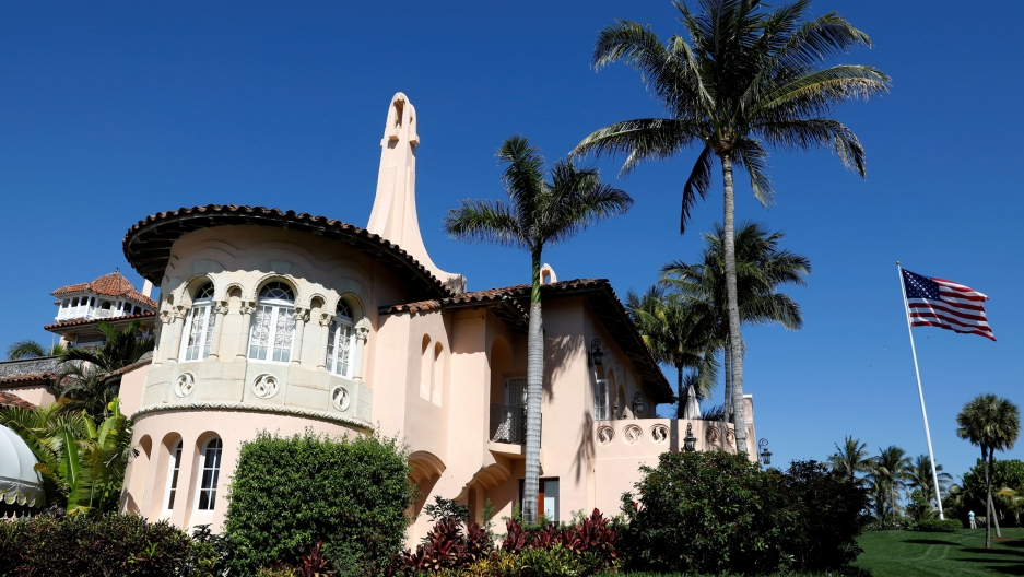 The Mar-a-Lago estate is shown in a medium shot photograph with peach-colored walls and a US flag flying to the right.