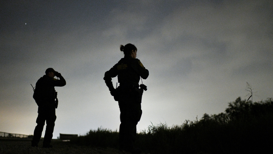 Two Border Patrol agents  are shown in silhouette looking off in a darkened field.