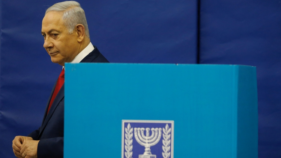 Israel's Prime Minister Benjamin Netanyahu is shown wearing a blue suit and walking past a blue voting booth.