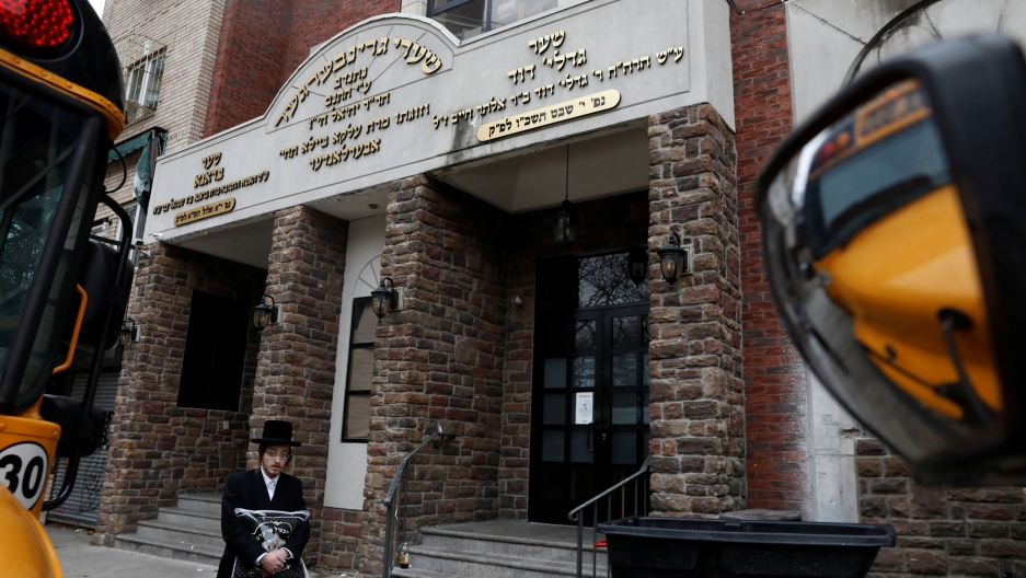 An Orthodox Jewish man is shown walking past the brick facade of the Yeshiva Kehilath Yakov school in Brooklyn.