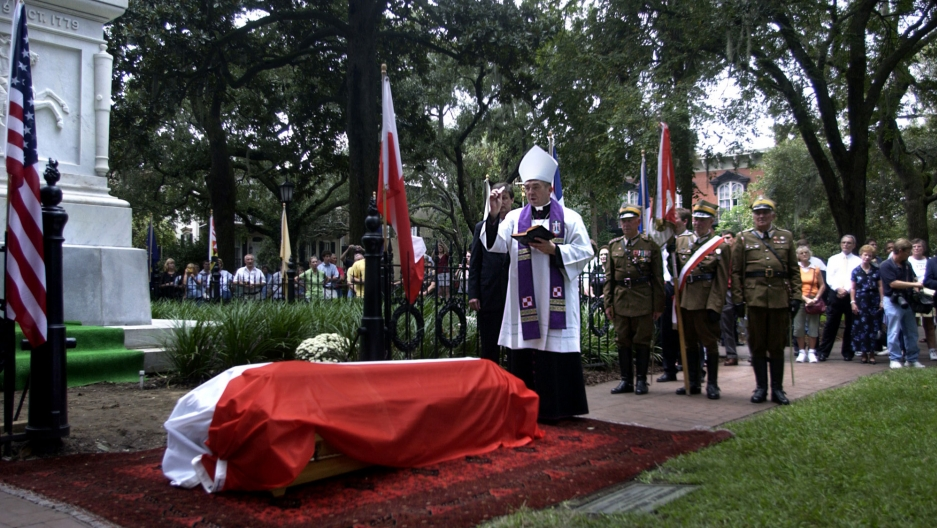 A bishop sprinkles holy water on a coffin covered in the Polish flag