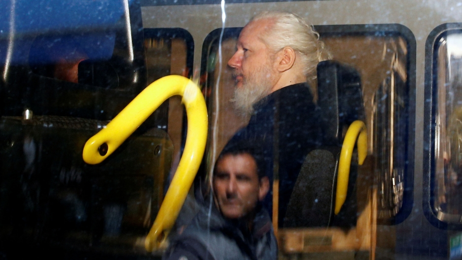 WikiLeaks founder Julian Assange is seen in profile sitting inside a police van in a photo taken through glass that has a reflection of a man.