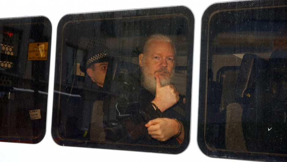 WikiLeaks founder Julian Assange is seen with a long white beard, sitting and handcuffed in a police van.