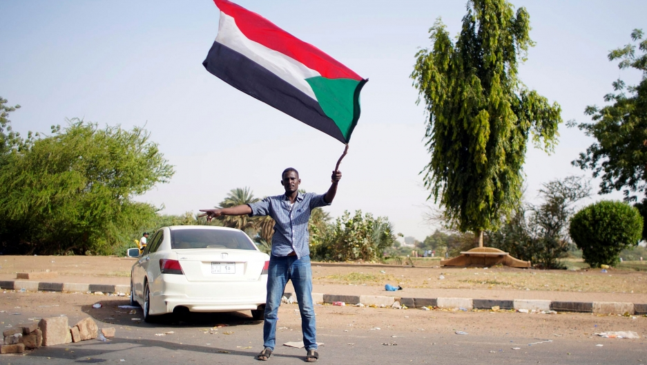 A man is shown wearing sandals, jeans and a button down shirt while waving the Sudanese flag.