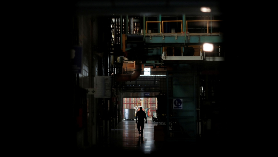 A man is shown in shadow walking past darked machinery.