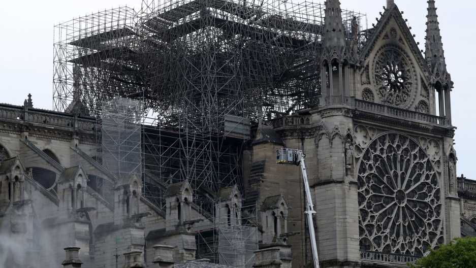 Smoke is seen rising around Notre-Dame Cathedral in Paris with some of the facade showing burn marks from the massive fire.