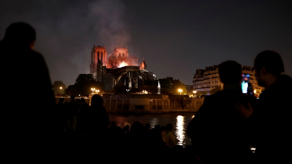 in the distance, the Notre Dame burns