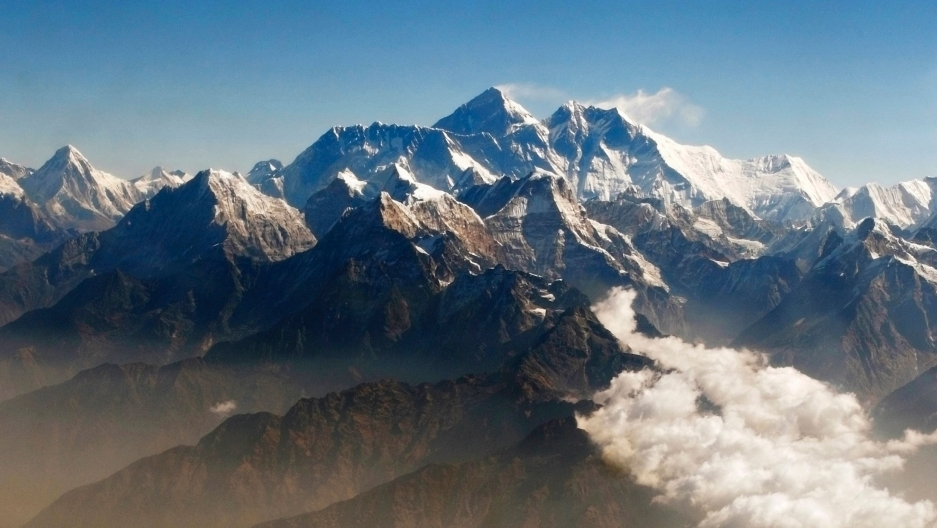 Mount Everest and the Himalayan mountain range covered in snow, seen from above.