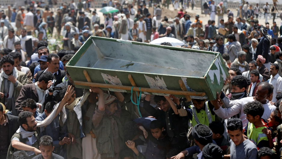 A group of people are shown carrying above their head an empty green coffin.
