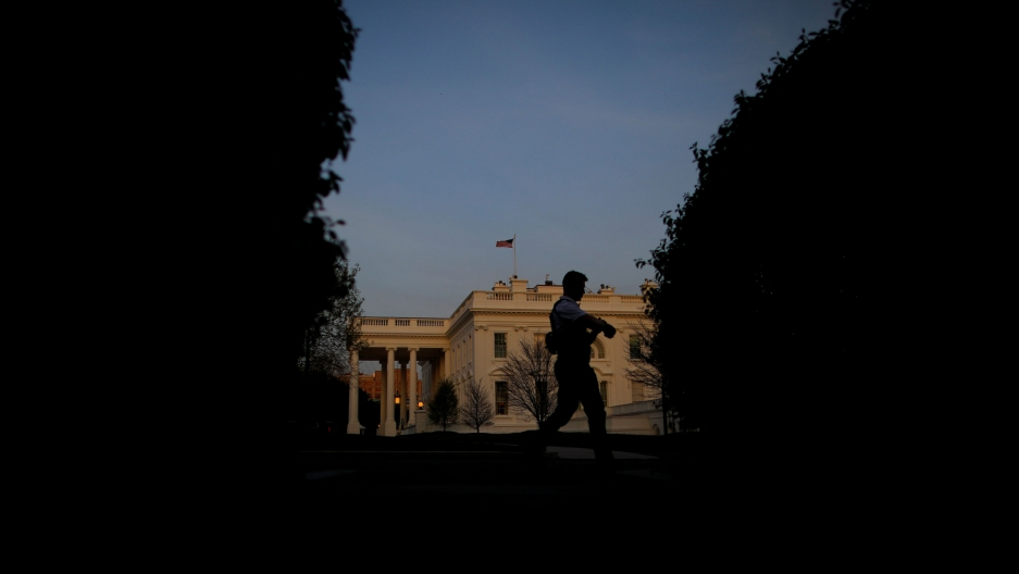 Secret Service agents are shown backlit, walking along the north lawn of the White House which is seen in the distance.