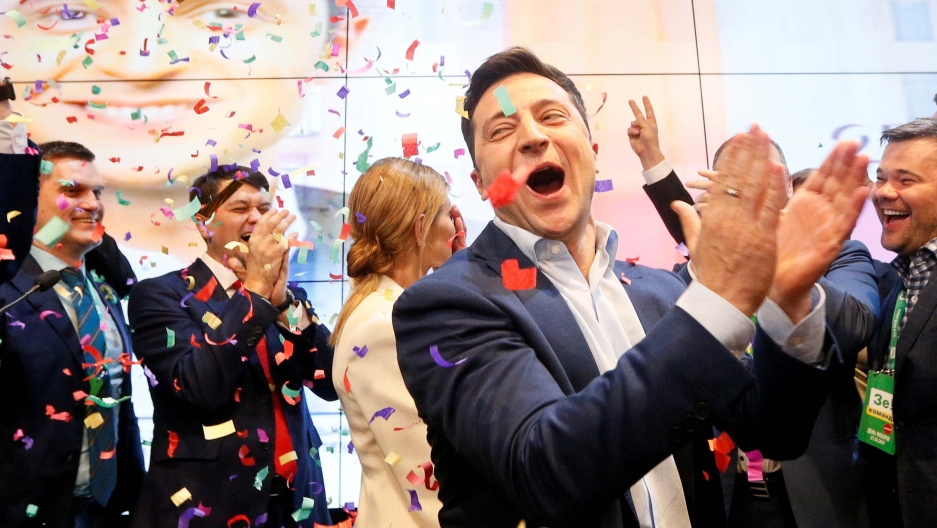 A man claps in the foreground as confetti floats through the air