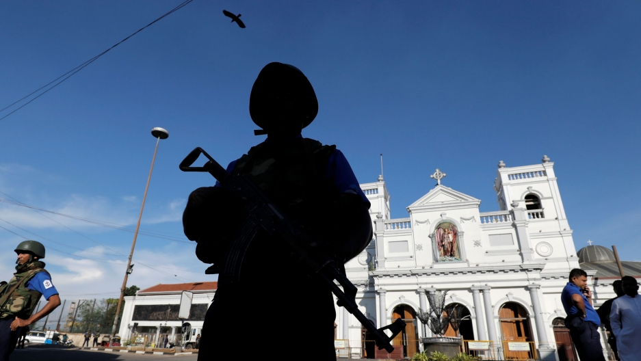 A security officer is shown standing in shadown and holding a gun with the white facade of St Anthony's shrine in the background.