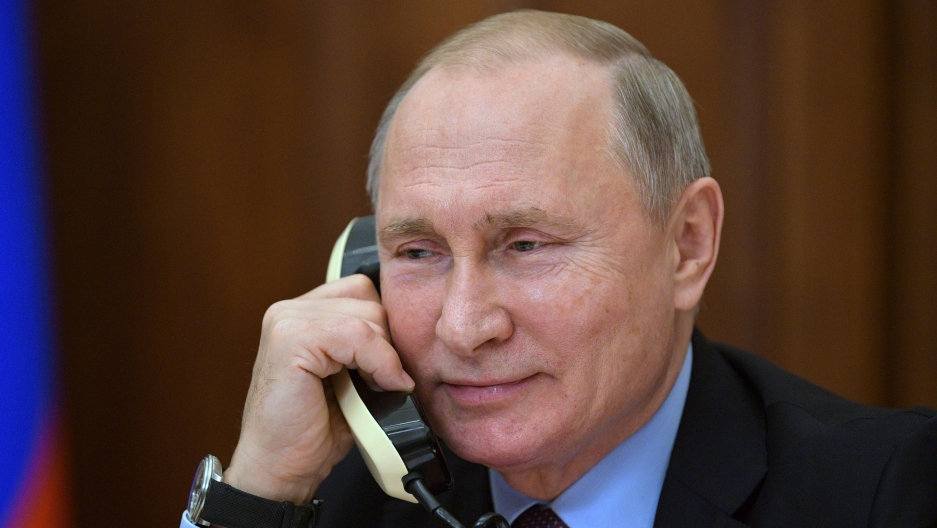 a smiling vladimir putin on the phone