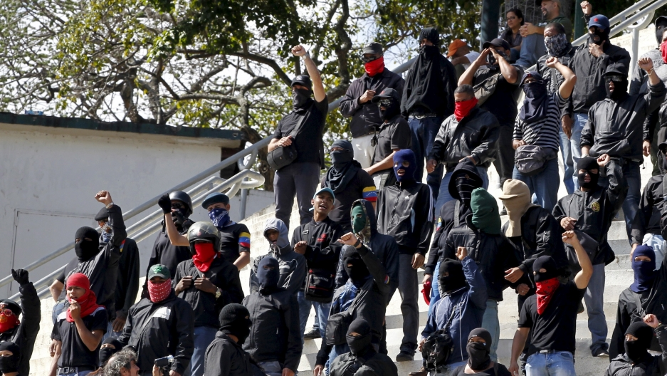 Young men wearing black stand on steps and raise fists in air.