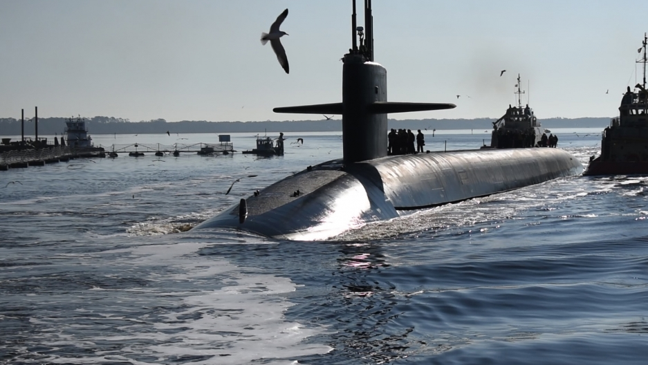 a submarine surfaces with bird flying overhead