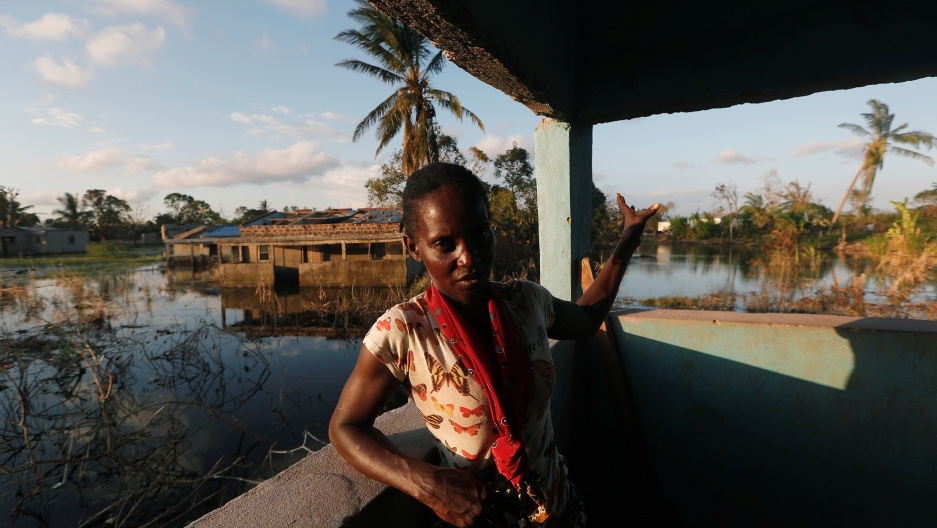 A woman stands near the corner of a house next to a flooded field.