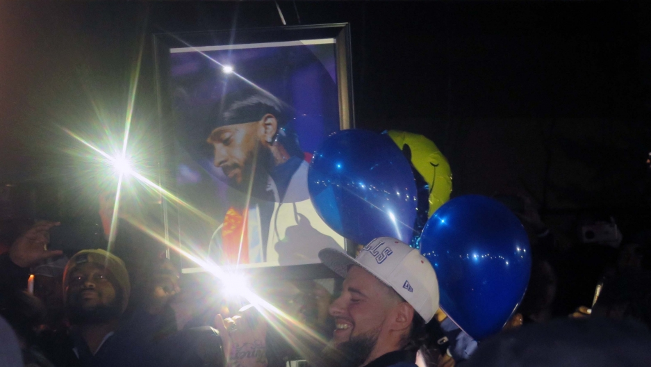 A framed photo of a black man is held by a crowd with balloons.