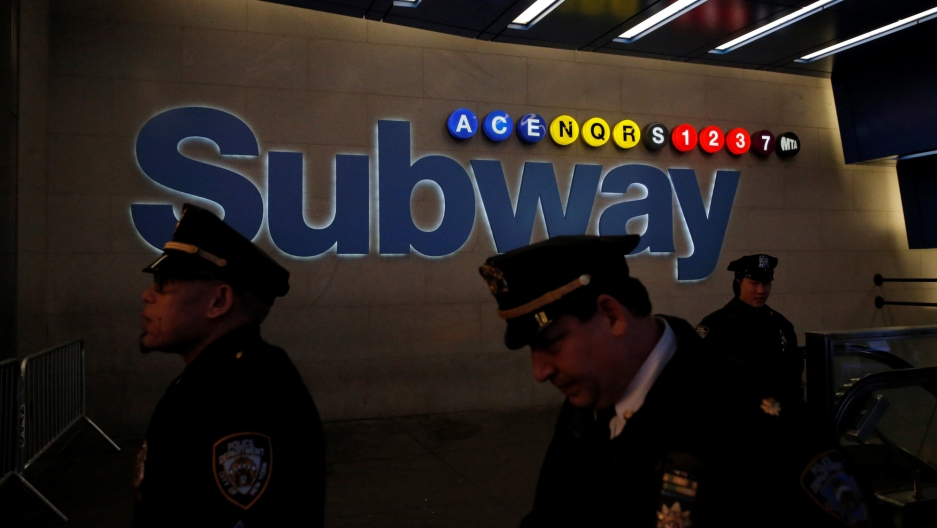 Members of the New York Police Department walk by a subway entrance on 42nd Street following an attempted detonation during the morning rush hour in New York City, Dec. 11, 2017.