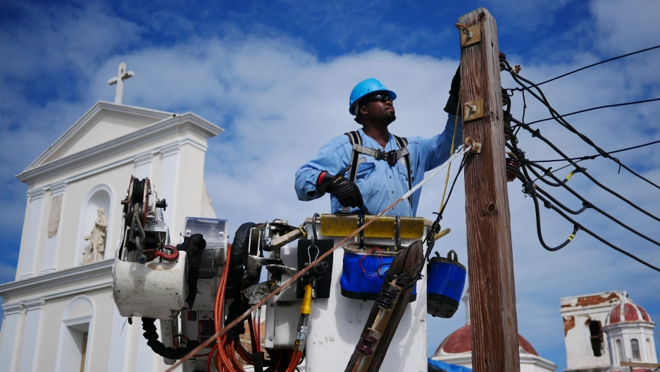 Marc Noisette of Westchester County, New York fixes the cables on an electric post opposite the Cathedral of San Juan in the historic quarter of Puerto Rico's capital.