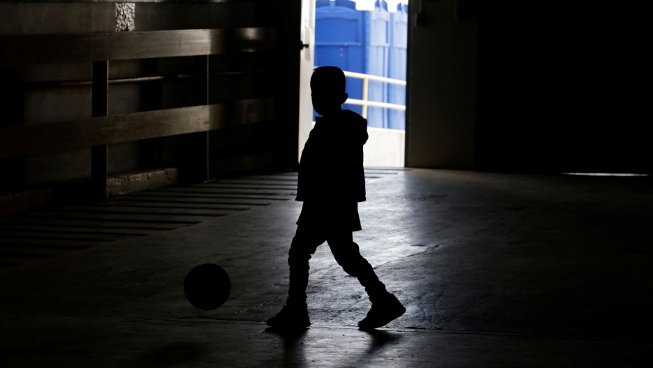A child is shown in shadow playing with a soccer ball inside a temporary shelter.