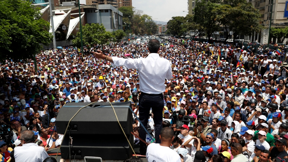Venezuelan opposition leader Juan Guaidó is photographed from behind speaking out to hundreds of supporters.