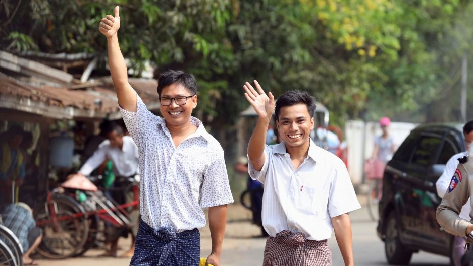 Reuters reporters Wa Lone and Kyaw Soe Oo are shown waving and giving the thumbs up sign while smiling.