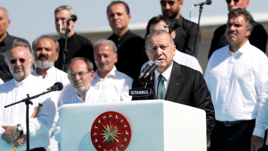 Turkish President Tayyip Erdoğan is shown making a speech behind a white podium with several stars on it.