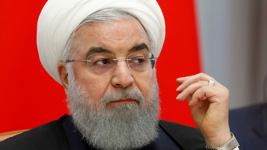 Iranian President Hassan Rouhani is shown in a close-up photograph wearing glasses and looking to his left.