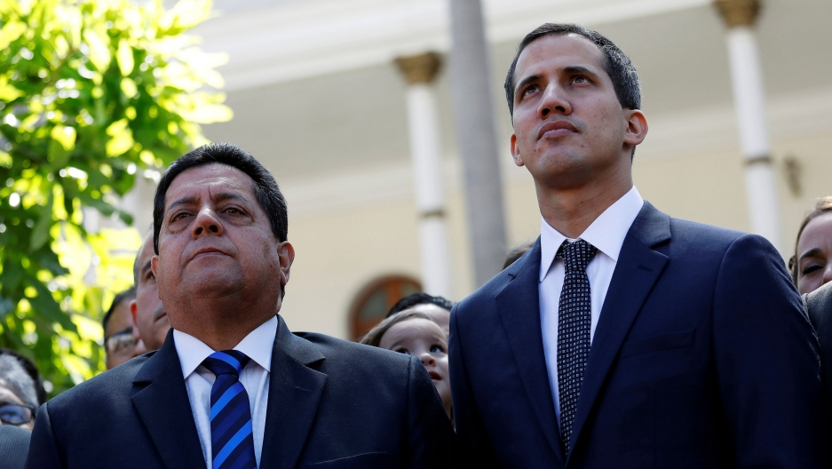 Venezuelan opposition leader Juan Guaidó (R) and lawmaker Edgar Zambrano are shown on a sunny day both wearing a suit and tie.