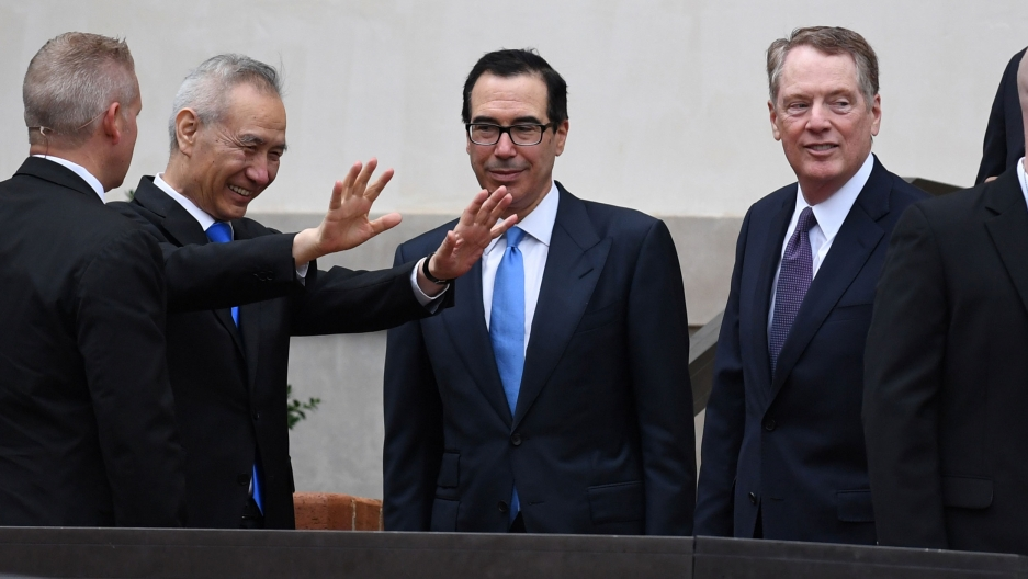 Chinese Vice Premier Liu He is shown with his hands outstretched and smiling next to Treasury Secretary Steven Mnuchin and Trade Representative Robert Lighthizer.