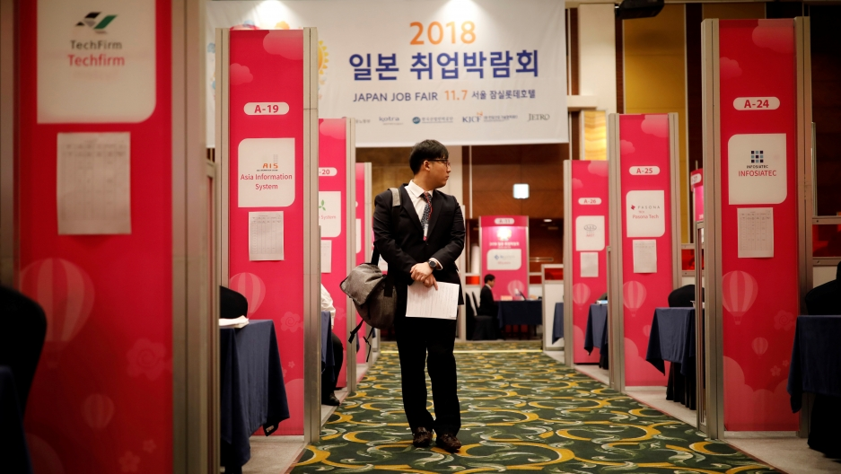A man walks along corridor between booths