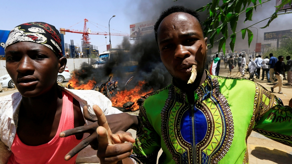 Two Sudanese men give a two-finger salute to the camera. Behind them a pile of tires is burning.