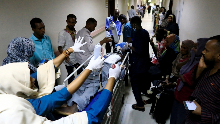 A gurney is rushed down a crowded hallway in a hospital