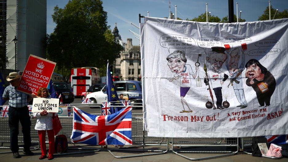A man and a woman with pro-Brexit signs stand next to a banner of political caricatures.