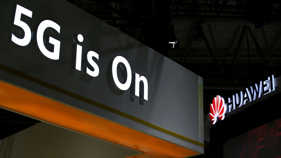 "A photo showing the corner of a exhibition booth with the words, ""5G is On"" illuminated in white."