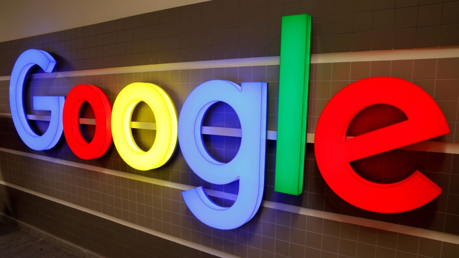 With letters that take up the entire frame of the photo, an illuminated Google logo is shown against a tile backdrop.