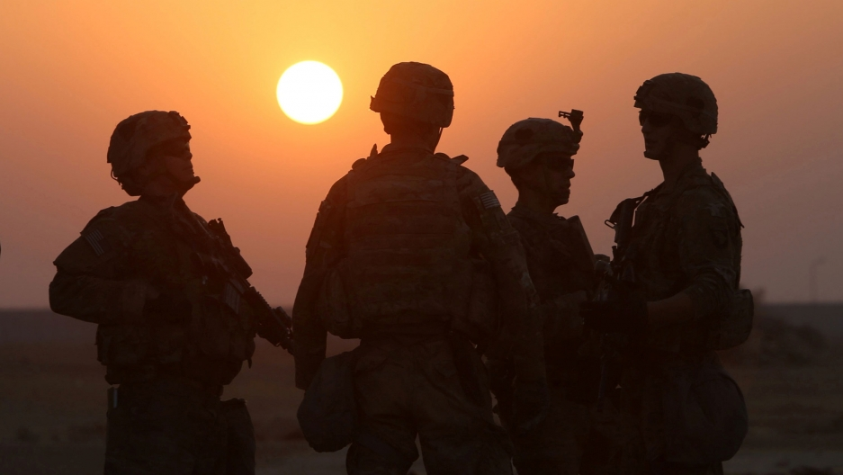 Four soldiers in full combat gear are seen in shadow with the setting sun behind them.