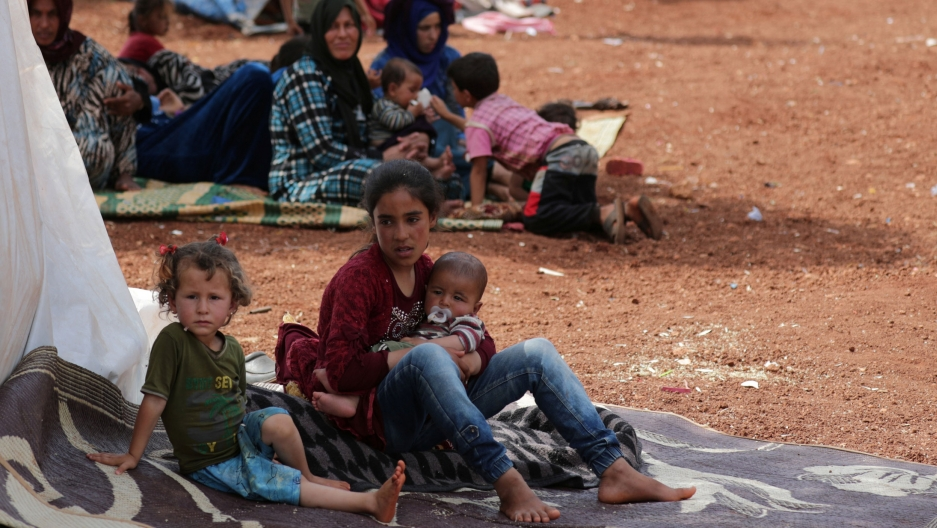 Two displaced Syrian girls is shown sitting on a mat and one holding a baby.