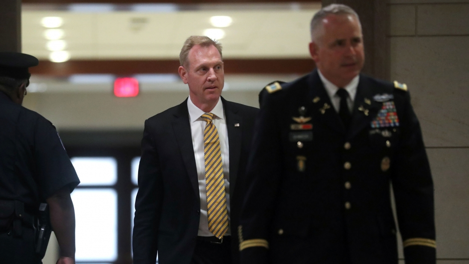 US Acting Defense Secretary Patrick Shanahan is shown walking in the background with a man in a US military uniform in the nearground.