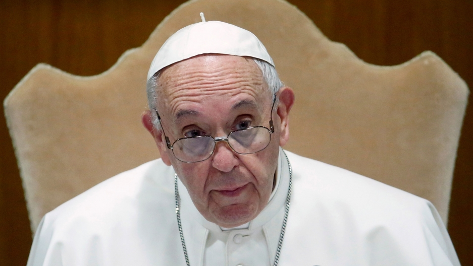 Pope Francis is shown sitting and looking to his left while wearing his traditional Papal attire.