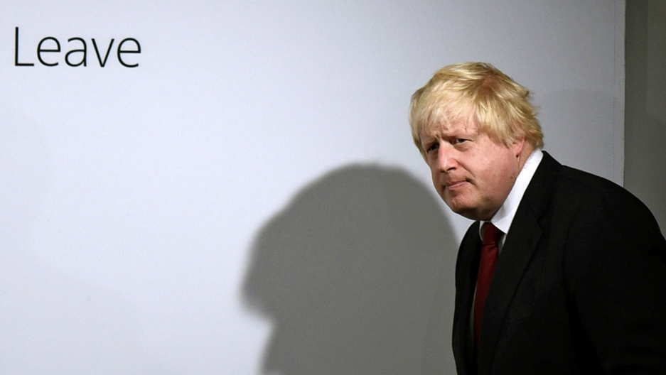 "Boris Johnson is shown walking in front of a white background with the word, ""Leave"" printed on it."