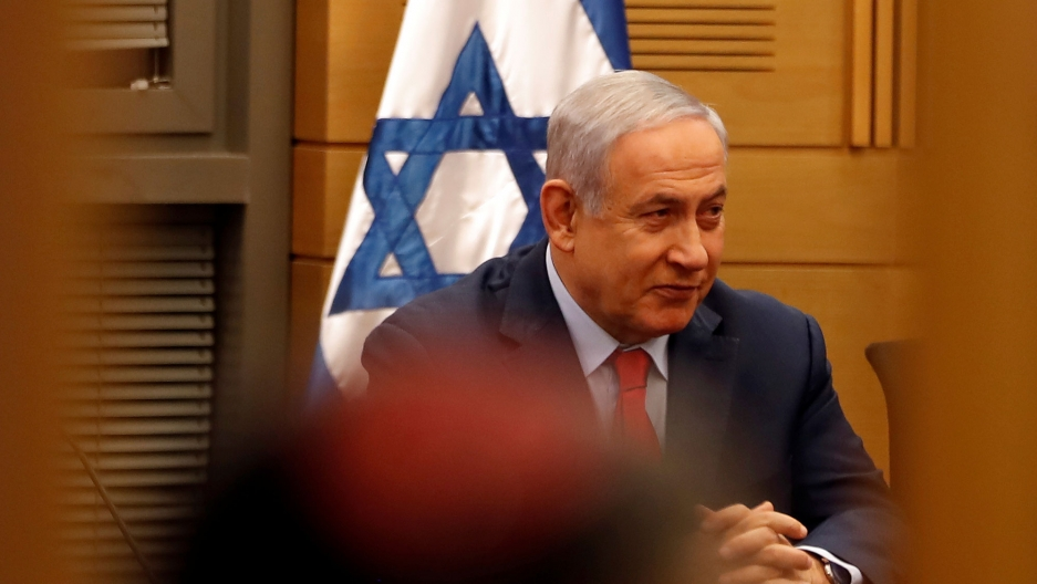 Israeli Prime Minister Benjamin Netanyahu is shown sitting with his hands folded and an Israeli flag behind him.