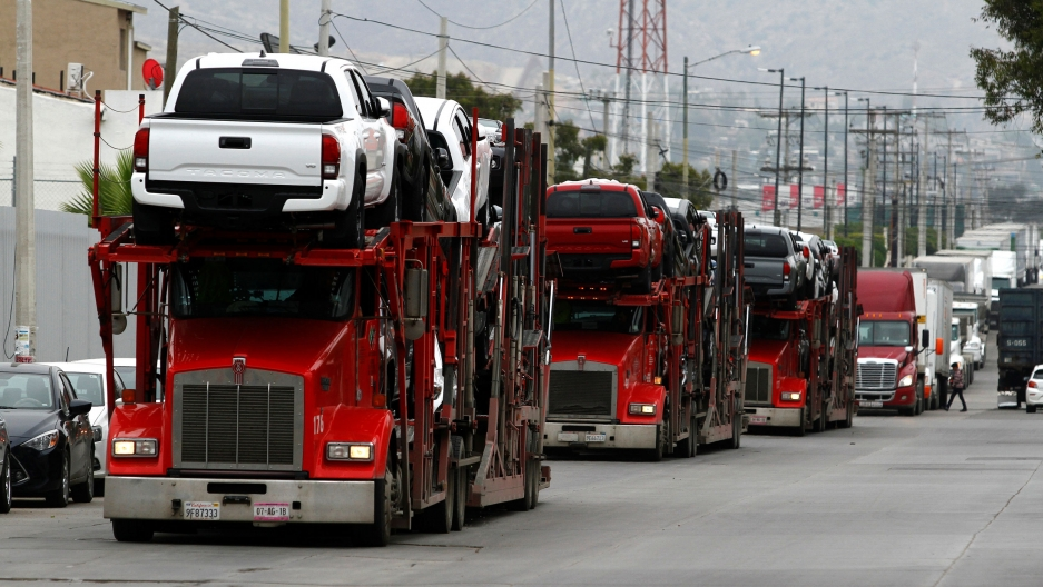 A long line of semi-trucks are shown waiting in line at the US-Mexico border.