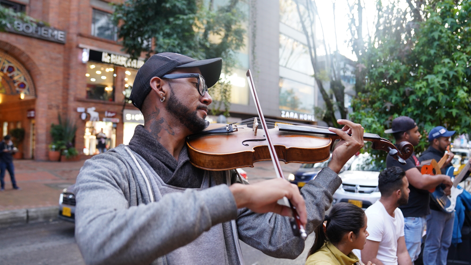 A young man with a neck tattoo and baseball cap plays violin on the street.