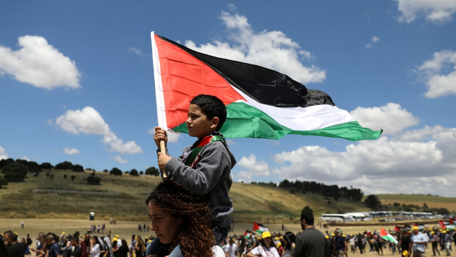 A young child sits on the shoulders of an adult waving a Palestinian flag under a blue sky