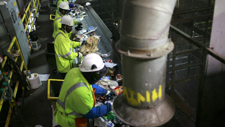 Workers in a dark building sort trash from a conveyor belt.