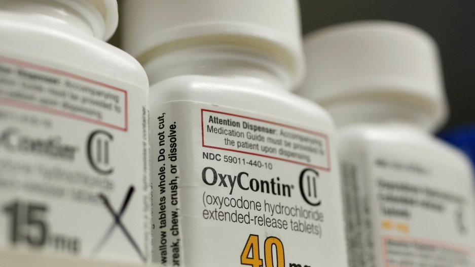 a white bottle of Oxycontin sits on a shelf.