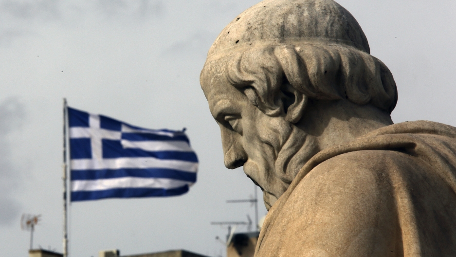 A marble statue stands in front of a Greek flag.